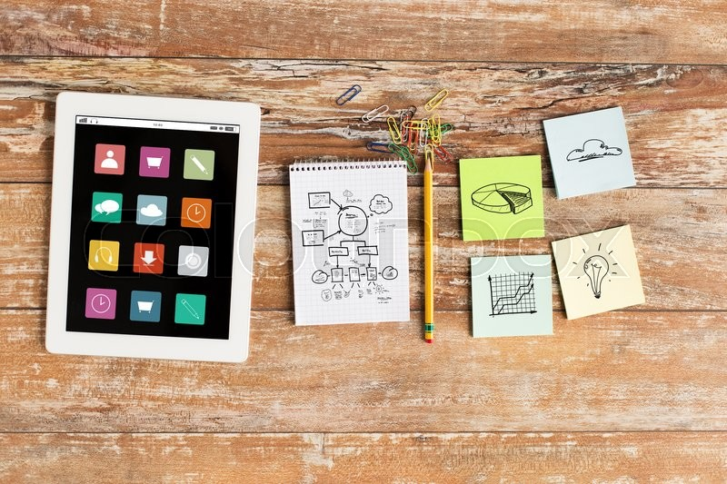 Stock image of 'business, multimedia, objects and technology concept - close up of notebook, tablet pc and stickers on table'