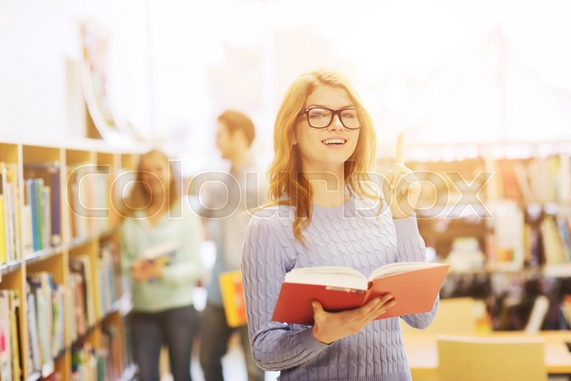 Stock image of 'people, knowledge, education and school concept - happy student girl or young woman with book in library'