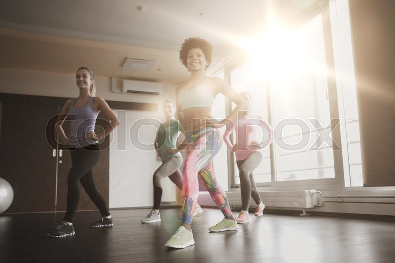 Stock image of 'fitness, sport, training, gym and lifestyle concept - group of happy women working out and stretching leg in gym'