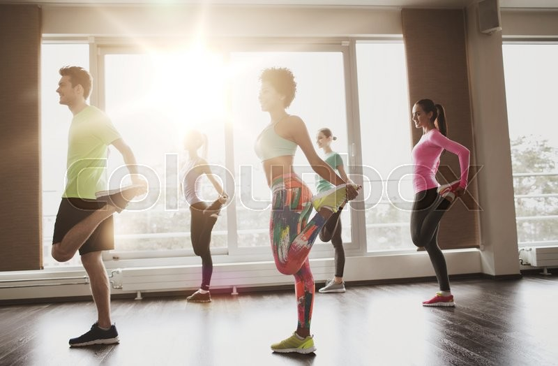 Stock image of 'fitness, sport, training, gym and lifestyle concept - group of smiling people with trainer exercising and stretching in gym'