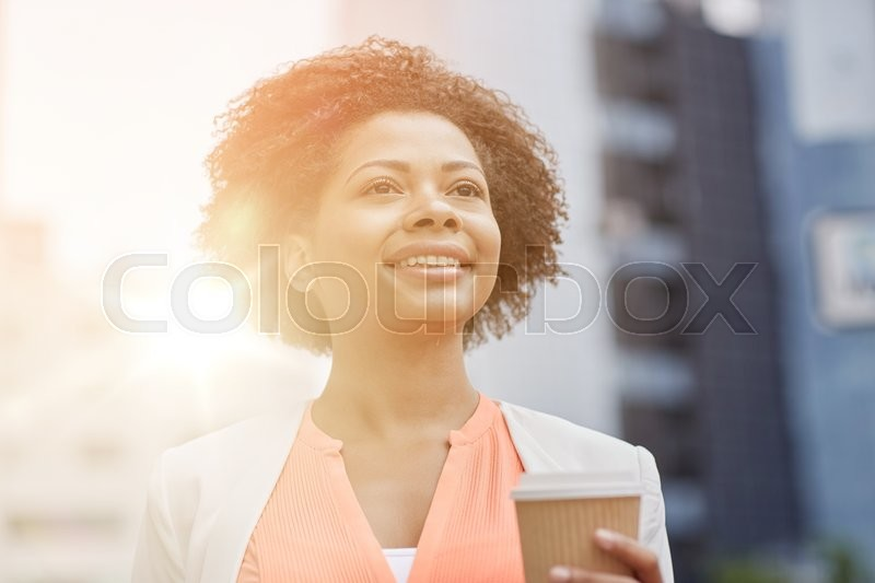 Stock image of 'business and people concept - young smiling african american businesswoman with coffee cup in city'