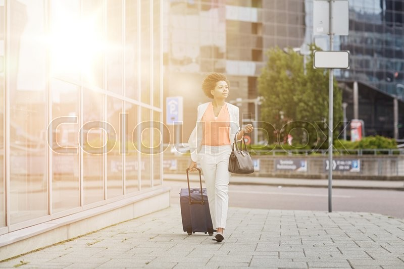 Stock image of 'travel, business trip, people and tourism concept - young african american  woman with travel bag walking down city street'