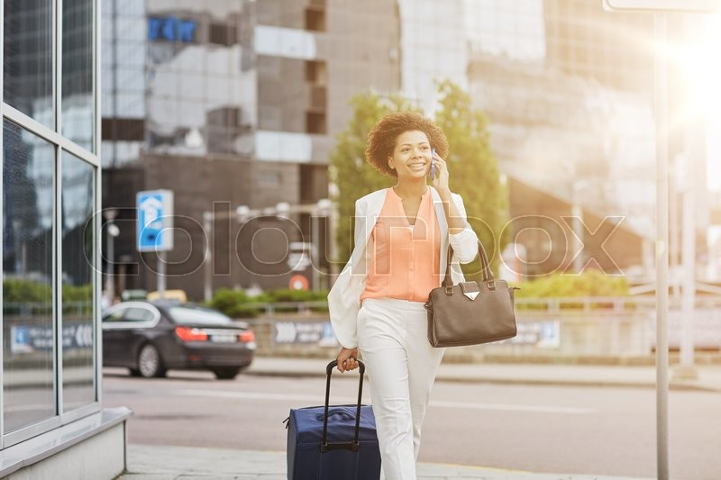 Stock image of 'travel, business trip, people and technology concept - happy young african american woman with travel bag walking down city street and calling on smartphone'