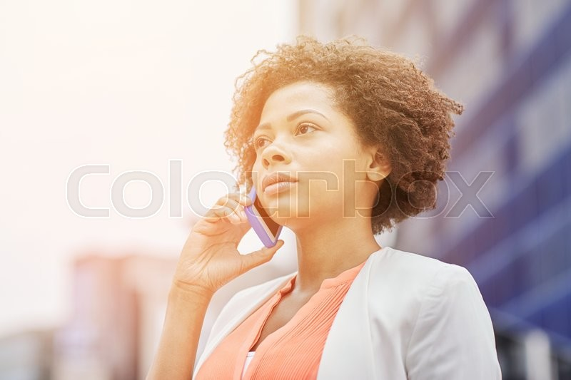 Stock image of 'business, communication, technology and people concept - young african american businesswoman calling on smartphone in city'