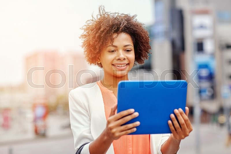 Stock image of 'business, technology, communication and people concept - young smiling african american businesswoman with tablet pc computer in city'