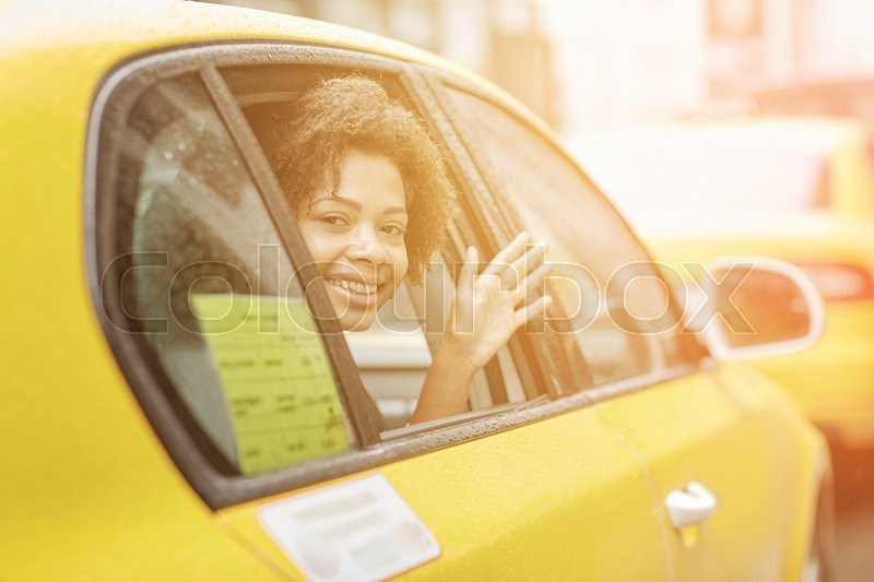 Stock image of 'business trip, transportation, travel, gesture and people concept - young smiling african american woman driving in taxi and waving hand at city street'