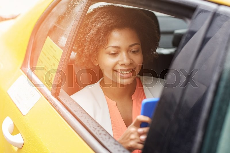 Stock image of 'business trip, transportation, travel, gesture and people concept - young smiling african american woman texing on smartphone in taxi at city street'