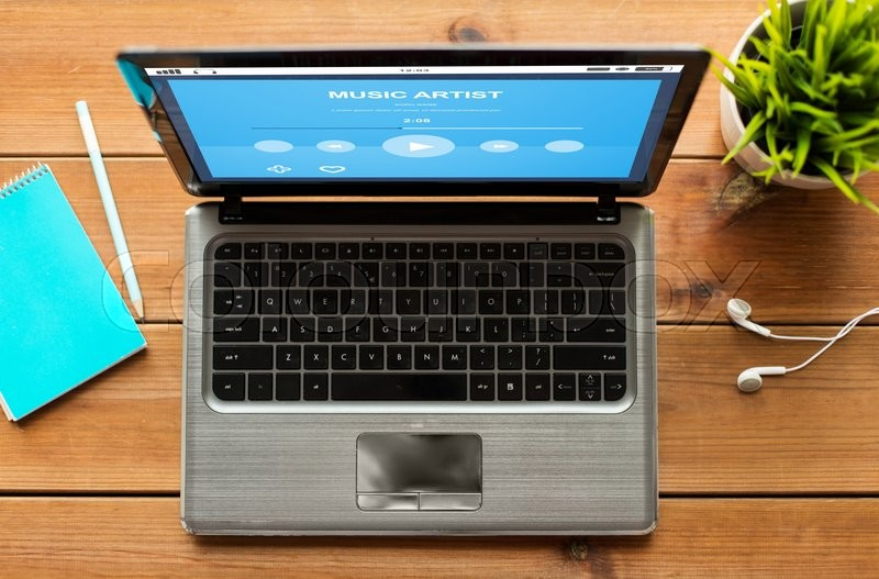 Stock image of 'education, business, multimedia and technology concept - close up of laptop computer with music player on screen on wooden table'