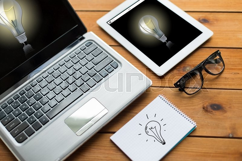 Stock image of 'education, business, startup and technology concept - close up of laptop computer, tablet pc and  notebook with eyeglasses and light bulbs on wooden table'