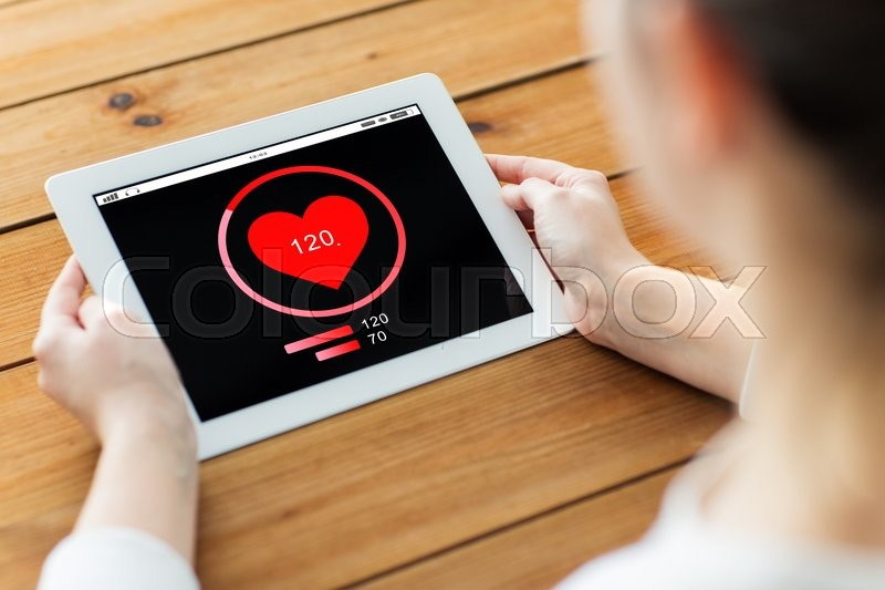 Stock image of 'technology, people and health care concept - close up of woman with heart rate on tablet pc computer screen on wooden table'