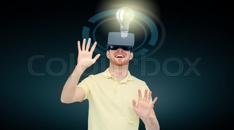 Stock image of '3d technology, virtual reality, cyberspace, entertainment and people concept - happy young man with virtual reality headset or 3d glasses playing game and looking at ligh bulb over black background'