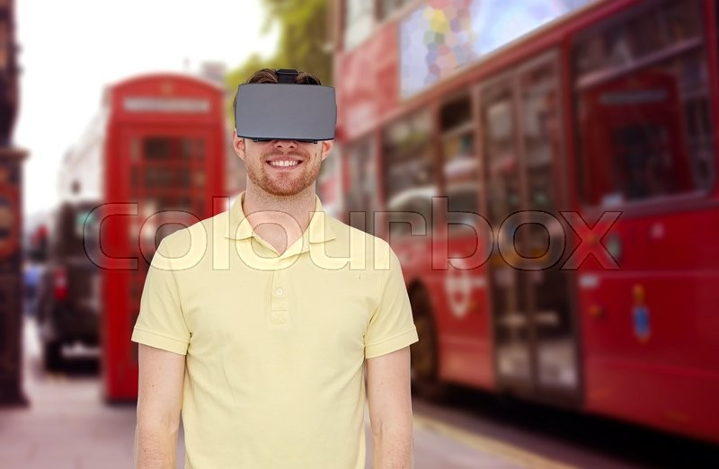 Stock image of '3d technology, virtual reality, travel, entertainment and people concept - happy young man with virtual reality headset or 3d glasses over london city street background'
