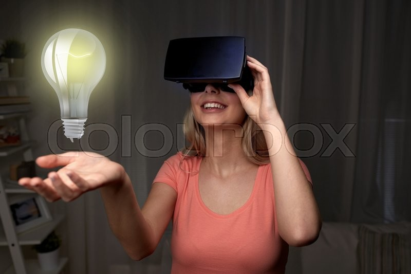 Stock image of 'technology, virtual reality, entertainment and people concept - happy young woman with virtual reality headset or 3d glasses playing game at home looking at light bulb projection'