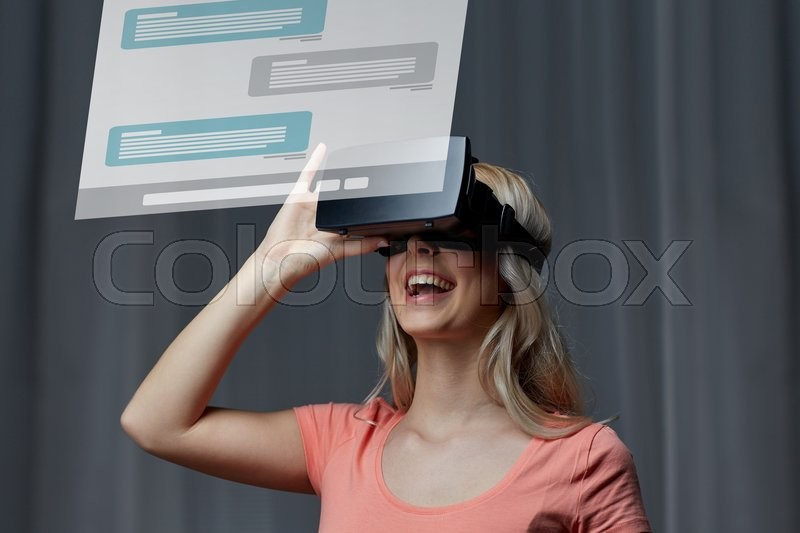 Stock image of 'technology, virtual reality, cyberspace, entertainment and people concept - happy young woman with virtual reality headset or 3d glasses at home looking at messenger chat projection'