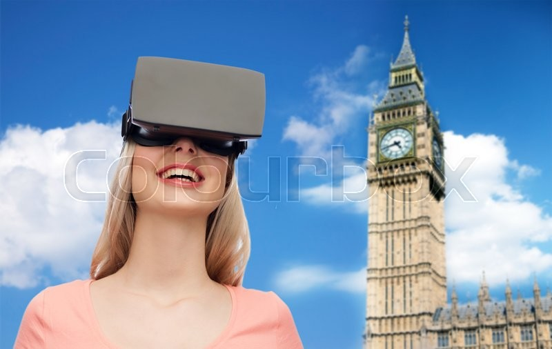 Stock image of 'technology, virtual reality, entertainment, travel and people concept - happy young woman with virtual reality headset or 3d glasses over big ben tower and sky background'