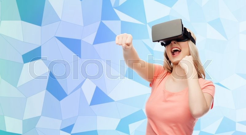Stock image of '3d technology, virtual reality, entertainment and people concept - happy young woman with virtual reality headset or 3d glasses playing game and fighting blue low poly texture background'