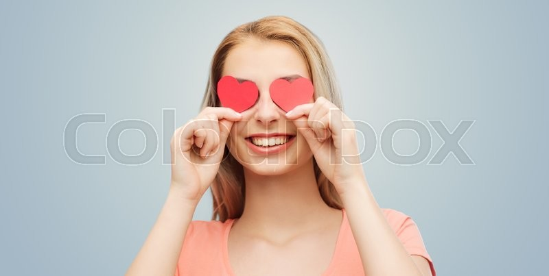 Stock image of 'love, romance, valentines day and people concept - smiling young woman or teenage girl with red heart shapes on eyes over gray background'