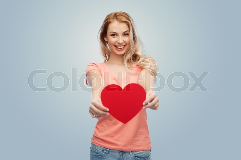 Stock image of 'love, romance, charity, valentines day and people concept - smiling young woman or teenage girl with blank red heart shape over gray background'