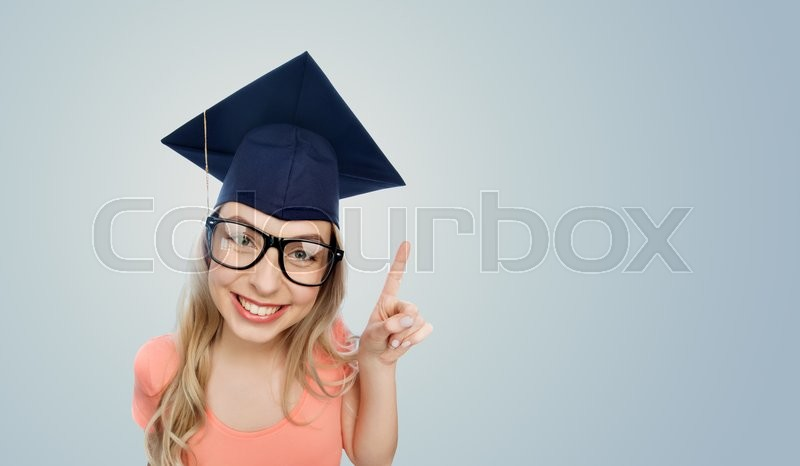 Stock image of 'people, graduation and education concept - smiling young student woman in mortarboard and eyeglasses pointing finger up over gray background'