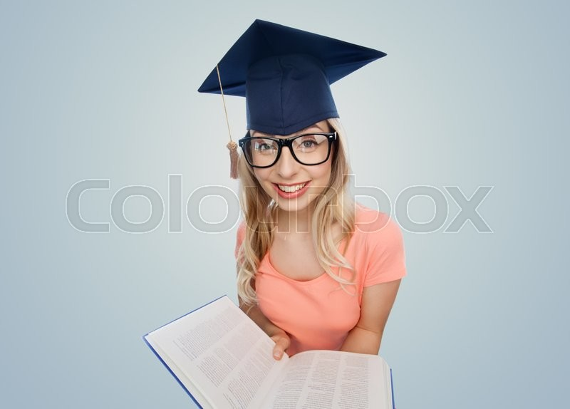 Stock image of 'people, education, knowledge and graduation concept - smiling young student woman in mortarboard and eyeglasses with encyclopedia book over gray background'