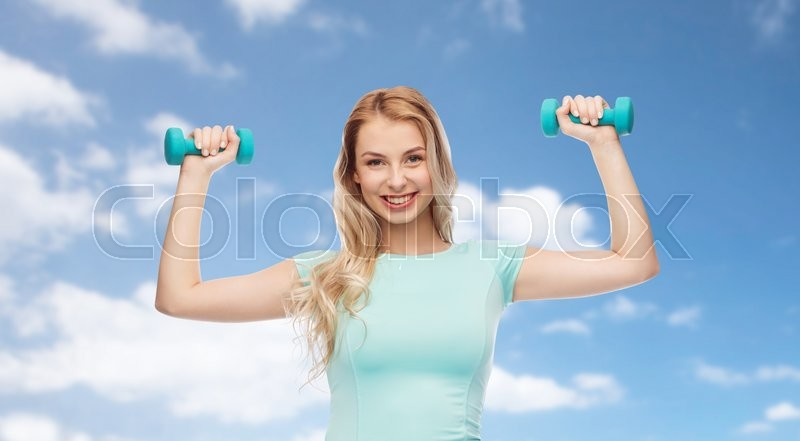 Stock image of 'fitness, sport, exercising and people concept - smiling beautiful sporty woman with dumbbell over blue sky and clouds background'
