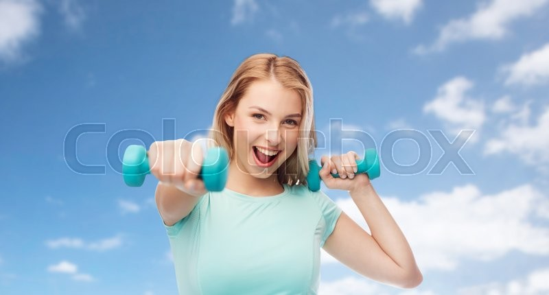 Stock image of 'fitness, sport, exercising and people concept - smiling beautiful sporty woman with dumbbell in fight stand over blue sky and clouds background'