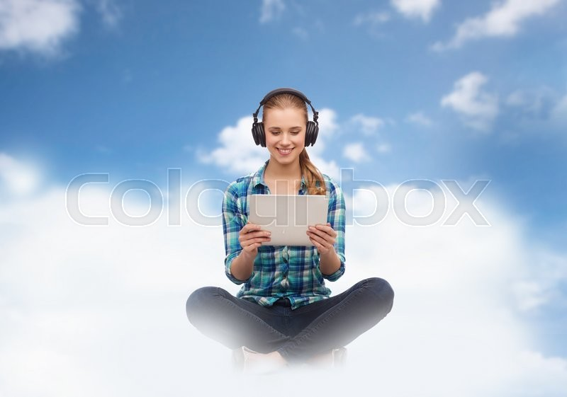 Stock image of 'music, technology, cloud computing and people concept - smiling woman sitting on the couch with tablet pc computer and headphones over blue sky and clouds background'