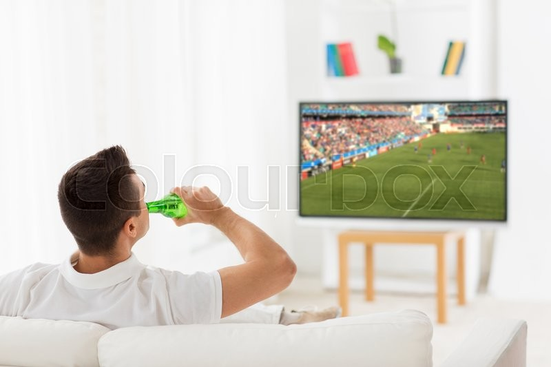 Stock image of 'leisure, technology, mass media and people concept - man watching football or soccer game on tv and drinking beer from bottle at home from back'