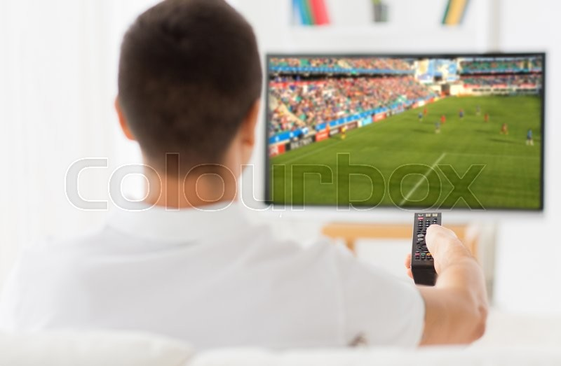 Stock image of 'leisure, technology, sport, entertainment and people concept - man with remote control watching football or soccer game on tv at home'