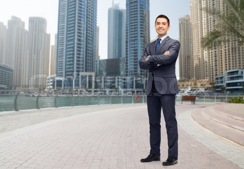 Stock image of 'business, people and office concept - happy smiling businessman in dark grey suit over dubai city street background'