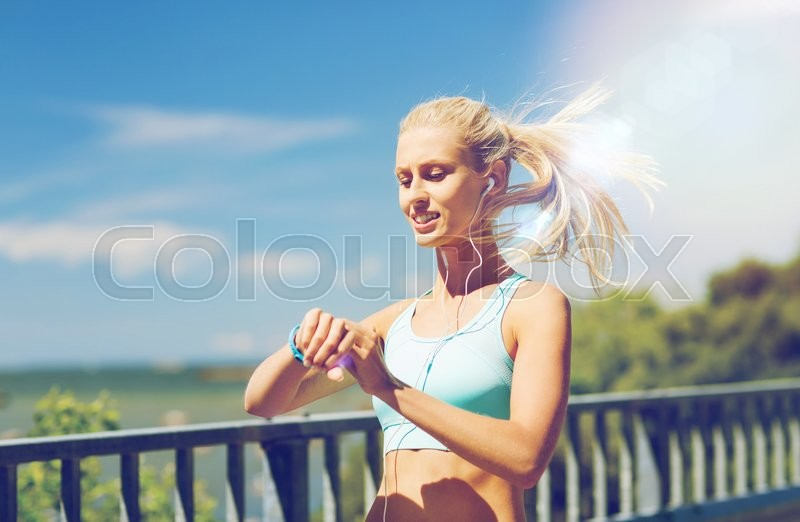 Stock image of 'fitness, sport, people, technology and healthy lifestyle concept - smiling young woman with heart rate watch and earphones exercising outdoors'