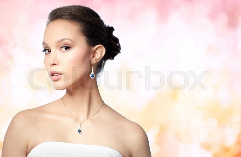 Stock image of 'beauty, jewelry, wedding accessories, people and luxury concept - beautiful asian woman or bride with earring and pendant over holidays lights background'