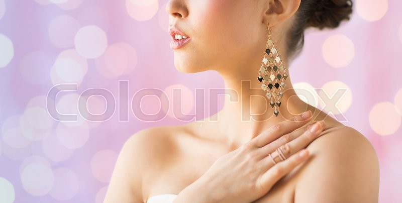 Stock image of 'glamour, beauty, jewelry and luxury concept - close up of beautiful woman with earrings over pink holidays lights background'