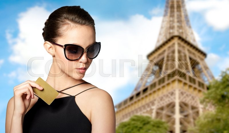Stock image of 'shopping tour, finances, travel, people and luxury concept - beautiful young woman in elegant black sunglasses with credit card over paris eiffel tower background'