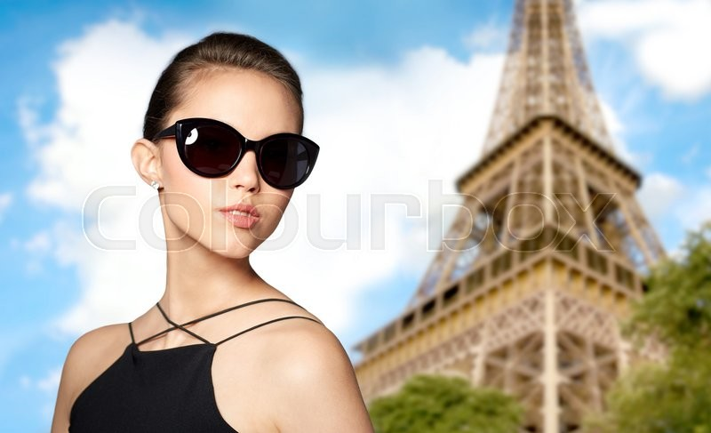 Stock image of 'accessories, eyewear, fashion, people and luxury concept - beautiful young woman in elegant black sunglasses over paris eiffel tower background'