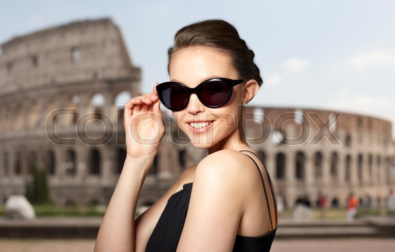 Stock image of 'accessories, eyewear, fashion, people and luxury concept - beautiful young woman in elegant black sunglasses over coliseum background'