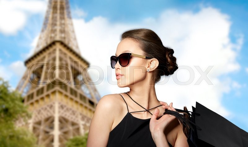 Stock image of 'sale, tour, fashion, people and luxury concept - happy beautiful young woman in black sunglasses with shopping bags over paris eiffel tower background'