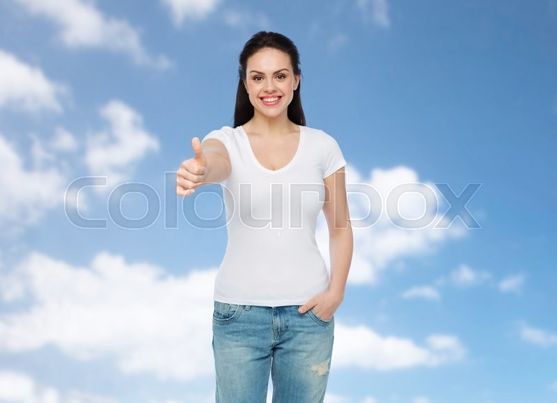 Stock image of 'advertisement, gesture, clothing and people concept - happy smiling young woman or teenage girl in white t-shirt showing thumbs up over blue sky and clouds background'