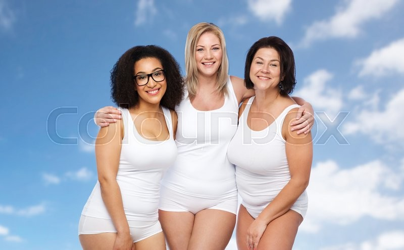 Stock image of 'friendship, beauty, body positive and people concept - group of happy plus size women in white underwear over blue sky and clouds background'