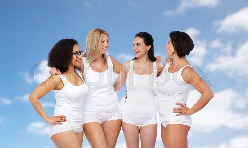 Stock image of 'friendship, beauty, body positive and people concept - group of happy women different in white underwear over blue sky and clouds background'