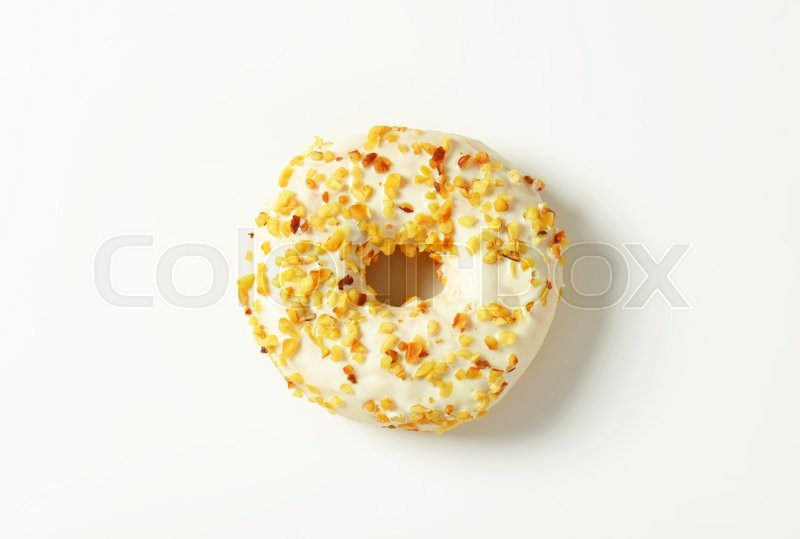 Stock image of 'Glazed donut topped with chopped nuts'
