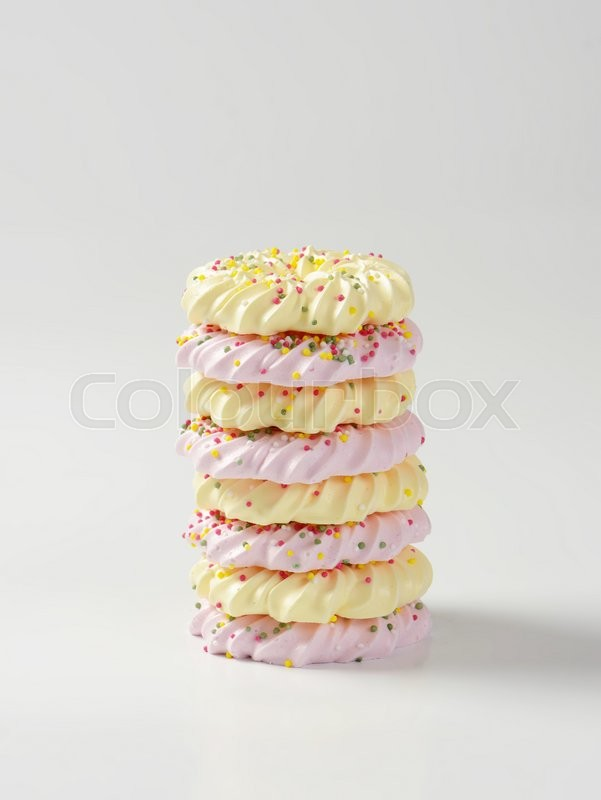 Stock image of 'Stack of wreath-shaped meringue cookies topped with sprinkles'