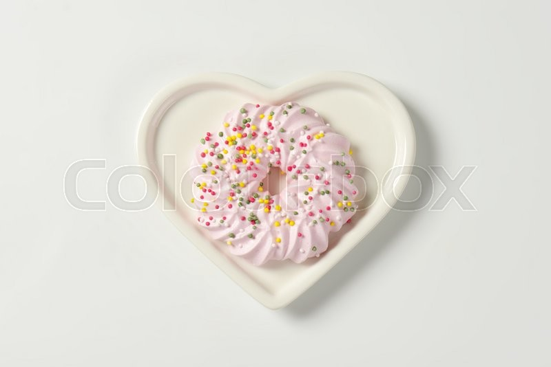 Stock image of 'Pink meringue wreath cookie topped with sprinkles on heart shaped plate'