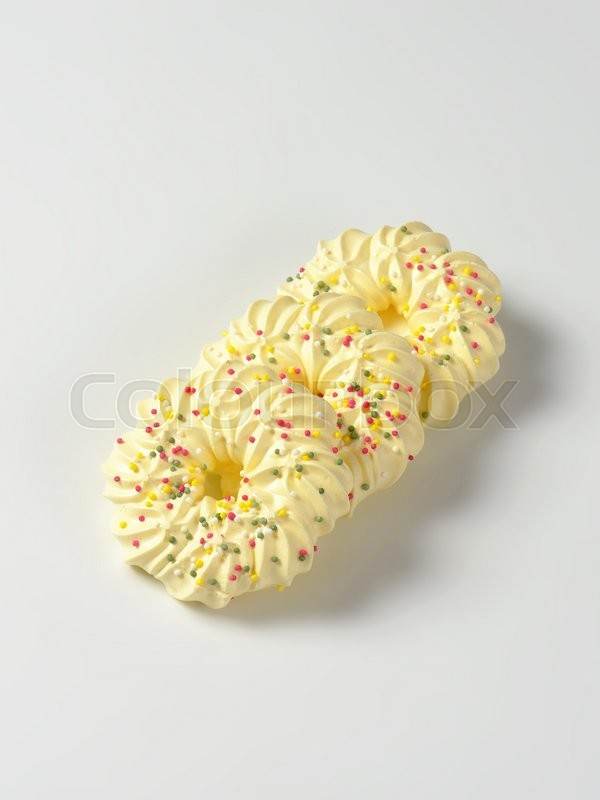 Stock image of 'Wreath-shaped meringue cookies topped with sprinkles'