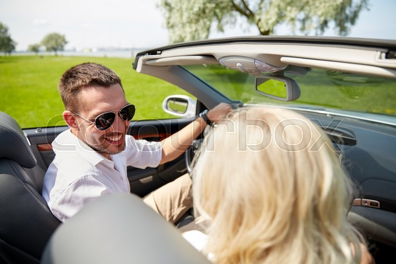 Stock image of 'leisure, road trip, dating, couple and people concept - happy man and woman driving in cabriolet car outdoors'
