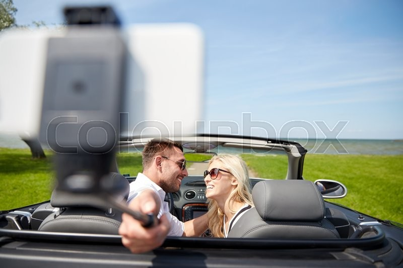 Stock image of 'road trip, travel, couple, technology and people concept - happy man and woman driving in cabriolet car and taking picture with smartphone on selfie stick'