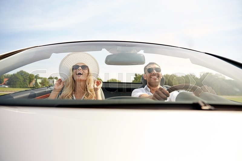 Stock image of 'road trip, travel, dating, couple and people concept - happy man and woman driving in cabriolet car outdoors'