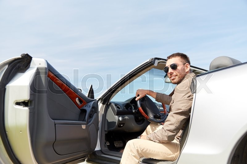 Stock image of 'road trip, travel, transport, leisure and people concept - happy man opening door of cabriolet car outdoors'