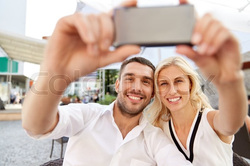 Stock image of 'love, date, technology, people and relations concept - smiling happy couple taking selfie with smatphone at restaurant terrace'