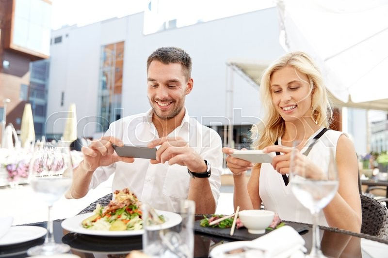 Stock image of 'love, date, technology, people and relations concept - happy couple with smatphone taking picture of food at restaurant terrace'
